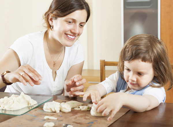 Mom helping her daughter bake cookies