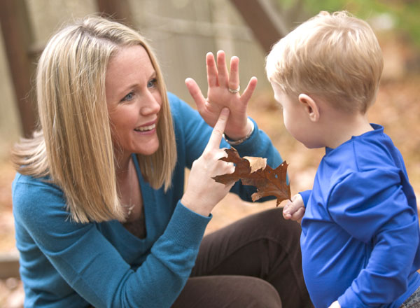 Mother giving sign language to her son